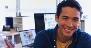 Sentada ejecutiva masculina en su escritorio en la oficina 4k almacen de metraje de vídeo