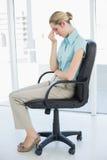 Sentada elegante de la empresaria agotada en su silla de eslabón giratorio Foto de archivo