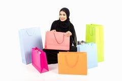 Sentada femenina árabe hermosa en el piso después de hacer compras Imagen de archivo libre de regalías