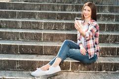 Sentada femenina alegre atractiva en las escaleras y takeaway del donante Imagen de archivo libre de regalías