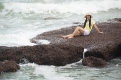 Sentada femenina bonita asiática en rocas con felicidad fuerte de la onda y de la relajación imágenes de archivo libres de regalías