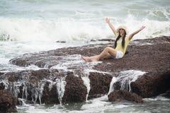 Sentada femenina bonita asiática en rocas con felicidad fuerte de la onda y de la relajación foto de archivo libre de regalías