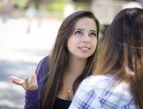 Sentada femenina de la raza mixta joven expresiva y el hablar con la muchacha Imagen de archivo libre de regalías