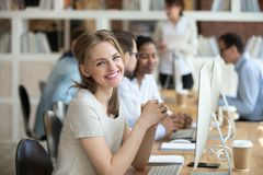 Sentada femenina del empleado en el escritorio enfrente de la PC que mira la cámara fotografía de archivo libre de regalías
