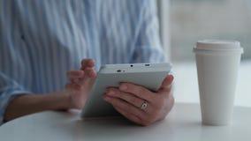 Sentada femenina en cafetería y usar la tableta digital metrajes