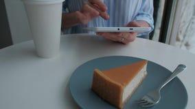 Sentada femenina en cafetería y usar la tableta digital almacen de metraje de vídeo
