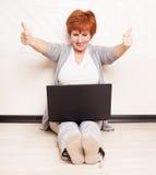 Sentada femenina en piso con el ordenador portátil Foto de archivo