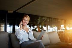 Sentada femenina feliz en el restaurante moderno interior y que habla en el teléfono móvil durante trabajo sobre la almohadilla t Imagen de archivo libre de regalías