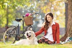 Sentada femenina hermosa en una hierba con su perro en un parque Fotos de archivo
