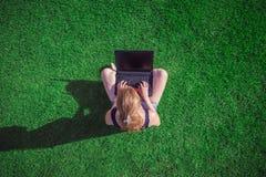 Sentada femenina joven en hierba y usar el ordenador portátil de la pantalla en blanco imagen de archivo libre de regalías