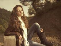 Sentada femenina joven en una cerca Imagen de archivo libre de regalías