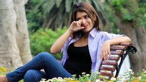 Sentada femenina joven llorosa en banco Foto de archivo libre de regalías