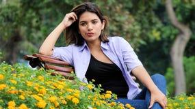 Sentada femenina joven preocupante en parque Fotografía de archivo