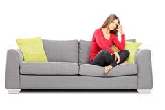 Sentada femenina joven triste en un sofá Foto de archivo