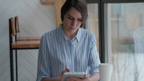 Sentada femenina linda en cafetería y usar la tableta digital metrajes