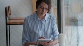 Sentada femenina linda en cafetería y usar la tableta digital almacen de metraje de vídeo
