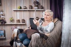 Sentada femenina mayor en sitio y Internet acogedores de la ojeada con TA Foto de archivo