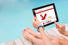 Sentada femenina por la piscina y la tecnología con para hacer compras en línea Fotos de archivo