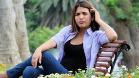 Sentada femenina preocupante en banco Imagen de archivo libre de regalías