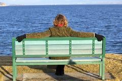 Sentada femenina solitaria en banco en el resorte imagen de archivo libre de regalías