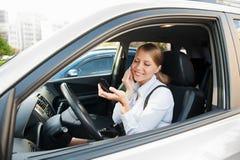 Sentada femenina sonriente en el coche Imágenes de archivo libres de regalías