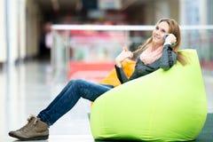 Sentada femenina sonriente en puf en oficina o centro comercial Foto de archivo libre de regalías