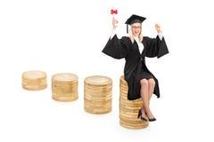 Sentada graduada de la hembra en una pila de monedas Fotos de archivo libres de regalías