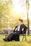 Sentada graduada relajada en un banco en parque Imágenes de archivo libres de regalías