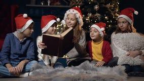 Sentada hermosa del libro de lectura de los niños cerca del árbol de navidad almacen de metraje de vídeo