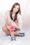 Sentada hermosa y sonrisa de la mujer joven Fotografía de archivo libre de regalías