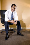 Sentada hispánica de mediana edad confidente del hombre de negocios Imágenes de archivo libres de regalías