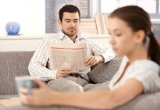 Sentada joven de los pares separada en sala de estar foto de archivo libre de regalías