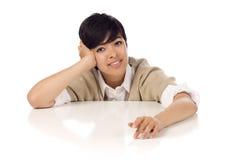Sentada joven sonriente de la hembra adulta de la raza mezclada Imagen de archivo