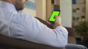 Sentada masculina barbuda en el sofá y el movimiento en sentido vertical en el teléfono móvil con la pantalla verde, app metrajes