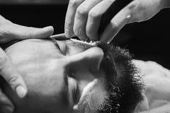 Sentada masculina barbuda en una butaca en una peluquería de caballeros mientras que el peluquero afeita su barba con una maquini fotografía de archivo