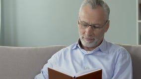 Sentada masculina envejecida en el sofá y la lectura un libro, tiempo de la reconstrucción después del retiro metrajes