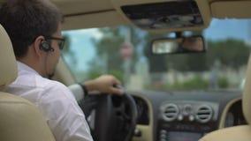 Sentada masculina joven en el asiento de conductores costoso de coche, pulgares-para arriba de la demostración, prueba de conducc almacen de metraje de vídeo