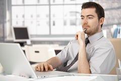 Sentada masculina joven en el escritorio que trabaja en la computadora portátil Fotos de archivo