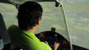 Sentada masculina joven en la carlinga, disfrutando de vuelo en simulador plano, afición almacen de video