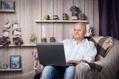 Sentada masculina mayor en sitio y Internet acogedores de la ojeada con el lapt Imagenes de archivo