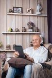 Sentada masculina mayor en sitio y Internet acogedores de la ojeada con el tabl Fotografía de archivo libre de regalías