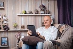 Sentada masculina mayor en sitio y Internet acogedores de la ojeada con el tabl Imagenes de archivo