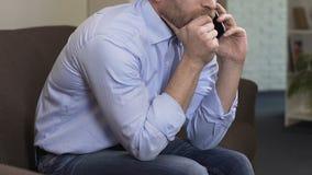 Sentada masculina triste en el sofá y el hablar en el teléfono móvil con la exnovia, crisis almacen de metraje de vídeo
