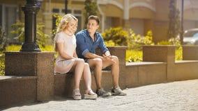 Sentada masculina y femenina en banco uno al lado del otro, sensación torpe, primera fecha imagen de archivo