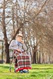Sentada mayor descontentada en una silla de ruedas en parque Fotografía de archivo