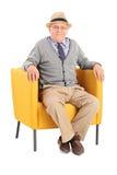 Sentada mayor en una butaca moderna y mirada de la cámara Foto de archivo libre de regalías