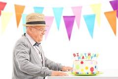Sentada mayor feliz en una tabla con la torta de cumpleaños Imagen de archivo libre de regalías