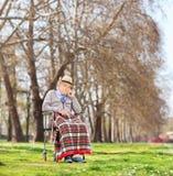 Sentada mayor preocupante en una silla de ruedas en parque Fotos de archivo