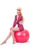 Sentada modelo del pinup rubio en bola de playa Fotografía de archivo libre de regalías