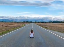 Sentada modelo en el camino recto largo con las montañas en distancia Imágenes de archivo libres de regalías